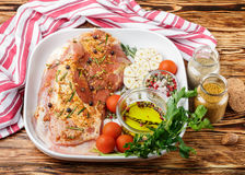 Fresh raw meat. Lamb with spices. Rosemary, juniper, garlic and tomatoes in a white ceramic form on a wooden table. The ingredients for a tasty dinner Stock Photos