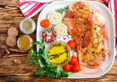 Fresh raw meat. Lamb with spices. Rosemary, juniper, garlic and tomatoes in a white ceramic form on a wooden table. The ingredients for a tasty dinner Stock Images