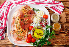 Fresh raw meat. Lamb with spices. Rosemary, juniper, garlic and tomatoes in a white ceramic form on a wooden table. The ingredients for a tasty dinner Royalty Free Stock Images