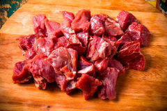 Fresh raw meat on light cutting board on an old wooden table. In. Gredients for traditional turkish meal - Kuru fasulye. Toned Royalty Free Stock Photo