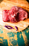 Fresh raw meat on light cutting board on an old wooden table. In. Gredients for traditional turkish meal - Kuru fasulye. Toned Stock Photo