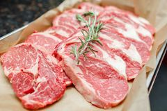Fresh raw meat on metal plate on dark table. Selective focus. Fresh raw meat on metal plate on dark table. Selective focus Stock Photo