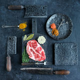 Fresh raw meat on metal serving. Fresh raw meat on black wooden cutting board surrounded by axes and knives and spices Stock Photos