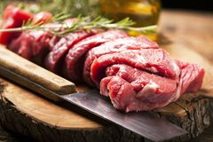 Fresh raw meat on old wooden table. Fresh raw meat on wooden board with knife Royalty Free Stock Image