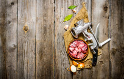Fresh raw meat in a onion with chopper, knife and spices on old fabric. On a wooden table. Free space for text . Top view Stock Photography