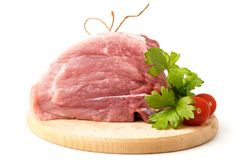 Fresh raw meat with parsley leaves and tomatoes. Fresh raw meat with parsley leaves and tomatoes on a wooden butcher Royalty Free Stock Photos