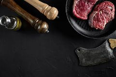 Fresh raw meat. A piece of beef tenderloin on grill pan, with a cutting ax, with spices for cooking on black stone table. Copy space. Top view. Still life Royalty Free Stock Images