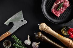Fresh raw meat. A piece of beef tenderloin on grill pan, with a cutting ax, with spices for cooking on black stone table. Copy space. Top view. Still life Stock Images