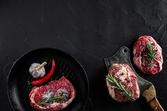 Fresh raw meat. A piece of beef tenderloin on grill pan, with a cutting ax, with spices for cooking on black stone table. Copy space. Top view. Still life Royalty Free Stock Photos