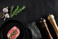 Fresh raw meat. A piece of beef tenderloin on grill pan, with a cutting ax, with spices for cooking on black stone table. Copy space. Top view. Still life Stock Image