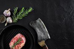 Fresh raw meat. A piece of beef tenderloin on grill pan, with a cutting ax, with spices for cooking on black stone table. Fresh raw meat. steak A piece of beef Stock Photos