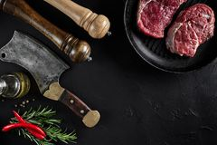 Fresh raw meat. A piece of beef tenderloin on grill pan, with a cutting ax, with spices for cooking on black stone table. Fresh raw meat steak. A piece of beef Stock Image