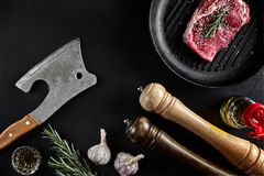 Fresh raw meat. A piece of beef tenderloin on grill pan, with a cutting ax, with spices for cooking on black stone table. Fresh raw meat. A piece of beef Stock Images