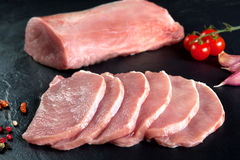 Fresh and raw meat. Pork tenderloin, loin medallions steaks in a row ready to cook. Background black blackboard