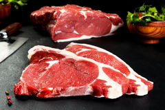 Fresh and raw meat. Ribeye. Uncooked steaks on black background blackboard. Fresh and raw meat. Ribeye. Two uncooked steaks on black slate background Royalty Free Stock Photos