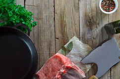 Fresh and raw meat. Ribs and pork chops on wooden background. Food background include fresh raw ribs and pork chops, pan, olive virgin oil, herbs, mix peas Royalty Free Stock Images