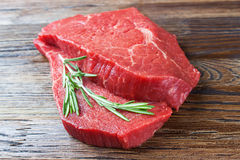 Fresh raw meat with rosemary. Fresh raw beef steak with rosemary on brown wooden table Royalty Free Stock Photos