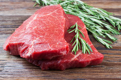 Fresh raw meat with rosemary. Fresh raw beef steak with rosemary on brown wooden table Royalty Free Stock Photo
