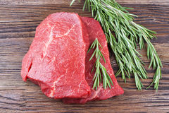 Fresh raw meat with rosemary. Fresh raw beef steak with rosemary on brown wooden table. Top view Royalty Free Stock Images