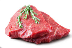 Fresh raw meat with rosemary. Fresh raw beef steak with rosemary isolated on white background Royalty Free Stock Images