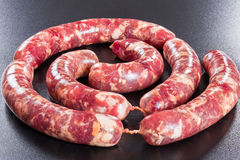 Fresh raw meat sausages on black background Stock Images