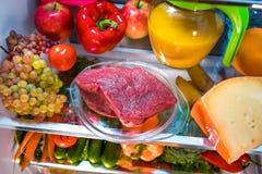 Fresh raw meat on a shelf open refrigerator Stock Photo