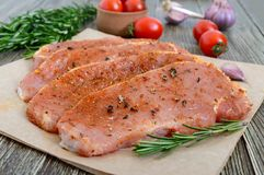 Fresh and raw meat. Sirloin steaks in a row ready to cook. Large pieces of raw meat in marinade with spices on paper on a wooden table Stock Photography