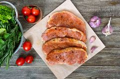 Fresh and raw meat. Sirloin steaks in a row ready to cook. Large pieces of raw meat in marinade with spices on paper on a wooden table.Top view Stock Photos