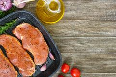 Fresh and raw meat. Sirloin steaks in a row ready to cook. Large pieces of raw meat in marinade with spices in the frying pan - grill on a wooden table.Top Royalty Free Stock Photos