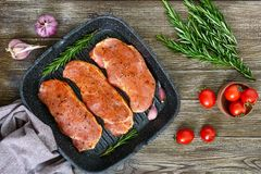Fresh and raw meat. Sirloin steaks in a row ready to cook. Large pieces of raw meat in marinade with spices in the frying pan - grill on a wooden table.Top Stock Image