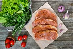 Fresh and raw meat. Sirloin steaks in a row ready to cook. Large pieces of raw meat in marinade with spices on paper on a wooden table.Top view Stock Photo