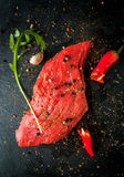 Fresh raw meat. Spices, chilli and garlic. Beef steak on black slate table. Top view Stock Photography