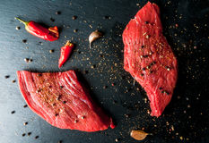 Fresh raw meat. Spices, chilli and garlic. Beef steak on black slate table. Top view Stock Images