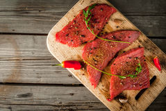 Fresh raw meat. Spices, chilli and garlic. Beef steak on a cutting board on a wooden table. Top view, copy space Stock Photo