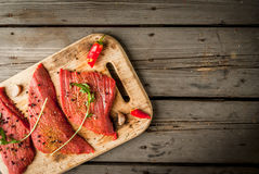 Fresh raw meat. Spices, chilli and garlic. Beef steak on a cutting board on a wooden table. Top view, copy space Royalty Free Stock Photos