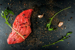 Fresh raw meat. Spices, chilli and garlic. Beef steak on a cutting board on a wooden table. Top view, copy space Royalty Free Stock Image
