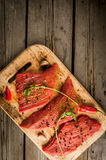 Fresh raw meat. Spices, chilli and garlic. Beef steak on a cutting board on a wooden table. Top view, copy space, vertical shot Stock Photography