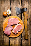 Fresh raw meat with spices and chopping axe. On wooden background. Top view Royalty Free Stock Photography