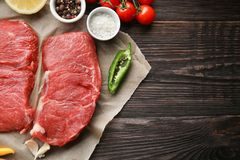 Fresh raw meat and spices. On wooden table Royalty Free Stock Image