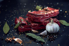 Fresh raw meat. Spices and garlic. On a cutting board on a black background. Top view, copy space Stock Image