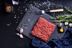 Fresh raw meat with spices. Ground beef steak . Fresh raw meat with spices. Ground beef steak on a dark table. Top view Royalty Free Stock Image