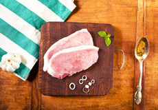 Fresh raw meat with spices. Fresh juicy steak with spices on the kitchen table, top view Stock Image