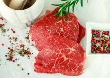 Fresh raw meat and spices. Marbled beef, rosemary and pepper on the table. The ingredients to prepare a delicious dinner. Selective focus Royalty Free Stock Images