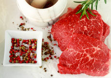 Fresh raw meat and spices. Marbled beef, rosemary and pepper on the table. The ingredients to prepare a delicious dinner. Selective focus Royalty Free Stock Photography