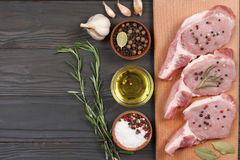 Fresh raw meat with spices on wooden table. top view with copy space. Fresh raw meat with spices on wooden background. top view with copy space Royalty Free Stock Image