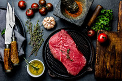 Fresh raw meat steak beef tenderloin, herbs and spices around cutting board. Food cooking background with copy space.  Royalty Free Stock Images