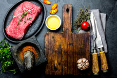 Fresh raw meat steak beef tenderloin, herbs and spices around cutting board. Food cooking background with copy space.  Stock Images