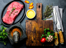 Fresh raw meat steak beef tenderloin, herbs and spices around cutting board. Food cooking background with copy space.  Stock Image