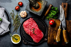Fresh raw meat steak beef tenderloin, herbs and spices around cutting board. Food cooking background with copy space.  Royalty Free Stock Photo