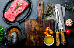 Fresh raw meat steak beef tenderloin, herbs and spices around cutting board. Food cooking background with copy space.  Stock Photo
